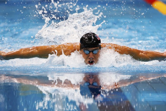 Michael Phelps of the U.S. is reflected as he swims his men's 100m butterfly semi-final during the London 2012 Olympic Games at the Aquatics Centre